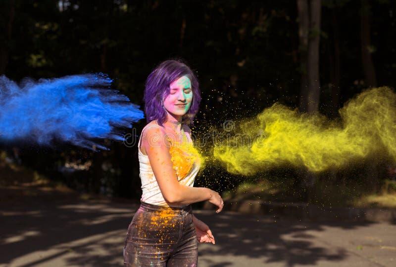 Aantrekkelijke vrouw met blauwe en gele Holi-poeder het exploderen arou stock fotografie