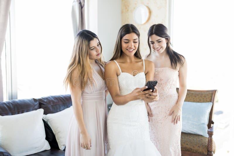 Aantrekkelijke Vrouw met Bruidsmeisjes die in Smartphone op Weddi bekijken stock fotografie