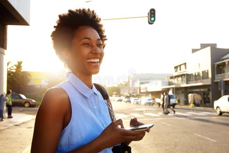 Aantrekkelijke vrouw met mobiele weg en telefoon die eruit zien lachen royalty-vrije stock afbeelding
