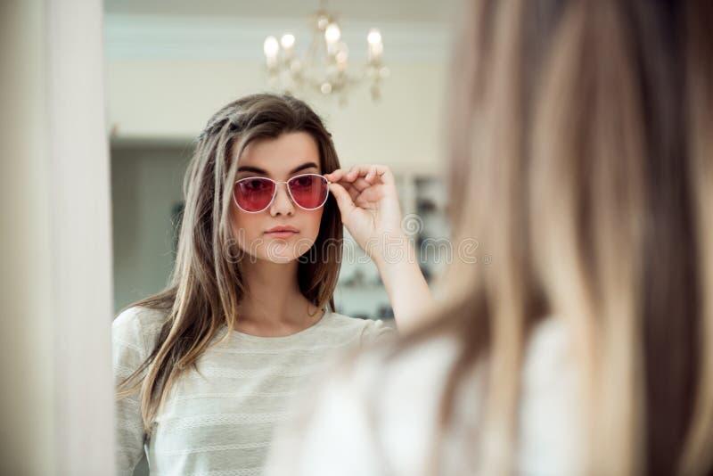 Aantrekkelijke vrouw op jacht voor nieuwe in dingen Binnenportret van modieuze jonge Kaukasische vrouw in opticienopslag stock afbeelding