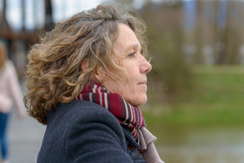 Aantrekkelijke vrouw op middelbare leeftijd diep in gedachte royalty-vrije stock afbeelding