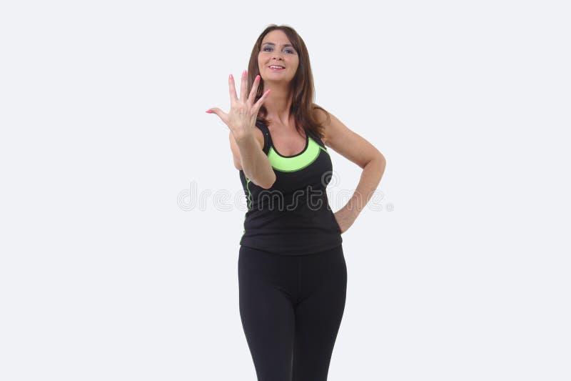 Aantrekkelijke vrouw op middelbare leeftijd in sportuitrusting die vijf vingers en het glimlachen steunen royalty-vrije stock fotografie