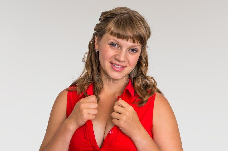 Aantrekkelijke vrouw in rode die kleding op grijze achtergrond wordt geïsoleerd royalty-vrije stock afbeelding