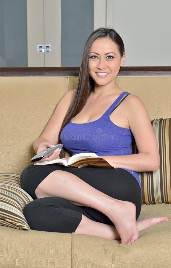 Aantrekkelijke vrouw thuis - het letten op TV royalty-vrije stock fotografie