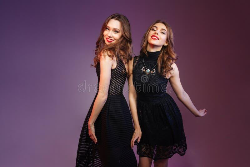 Aantrekkelijke vrouw twee die op partij over purpere achtergrond dansen stock foto
