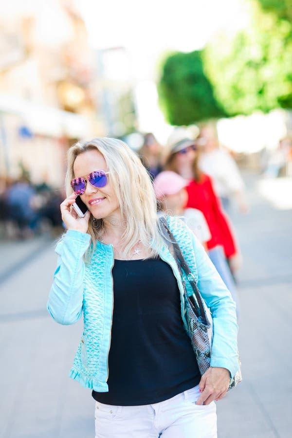 Aantrekkelijke vrouw in zonglazen die de stad in en celtelefoon lopen met behulp van stock foto