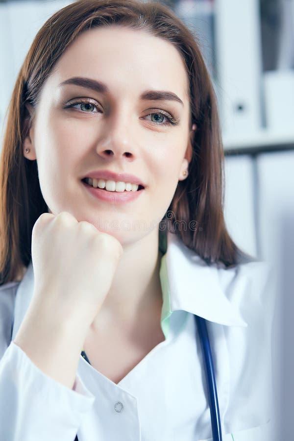 Aantrekkelijke vrouwelijke arts die aan haar laptop in haar bureau werken Gelukkige arts die op patiënt wachten royalty-vrije stock foto's