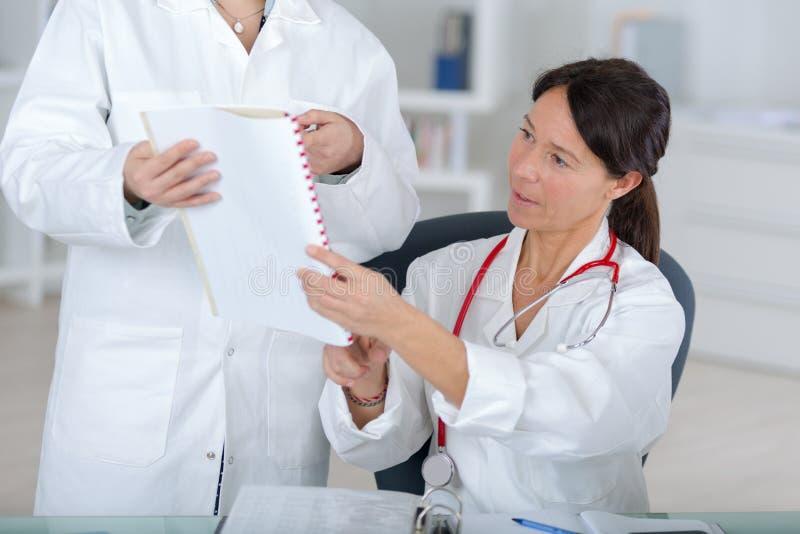 Aantrekkelijke vrouwelijke arts die coleague op artsenkantoor raadplegen stock afbeelding