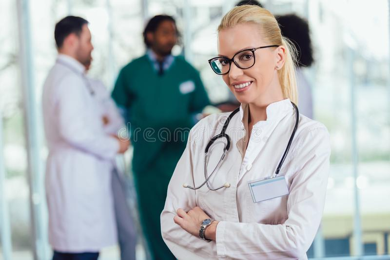 Aantrekkelijke vrouwelijke arts die op het ziekenhuisgang camera het glimlachen bekijken stock afbeelding
