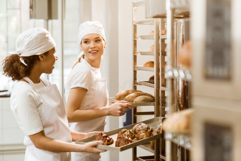 aantrekkelijke vrouwelijke bakkers die vers gebakje op planken zetten stock fotografie