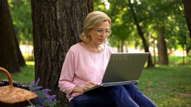 Aantrekkelijke vrouwelijke gepensioneerdezitting in park met laptop en het surfen van netto, app stock foto's