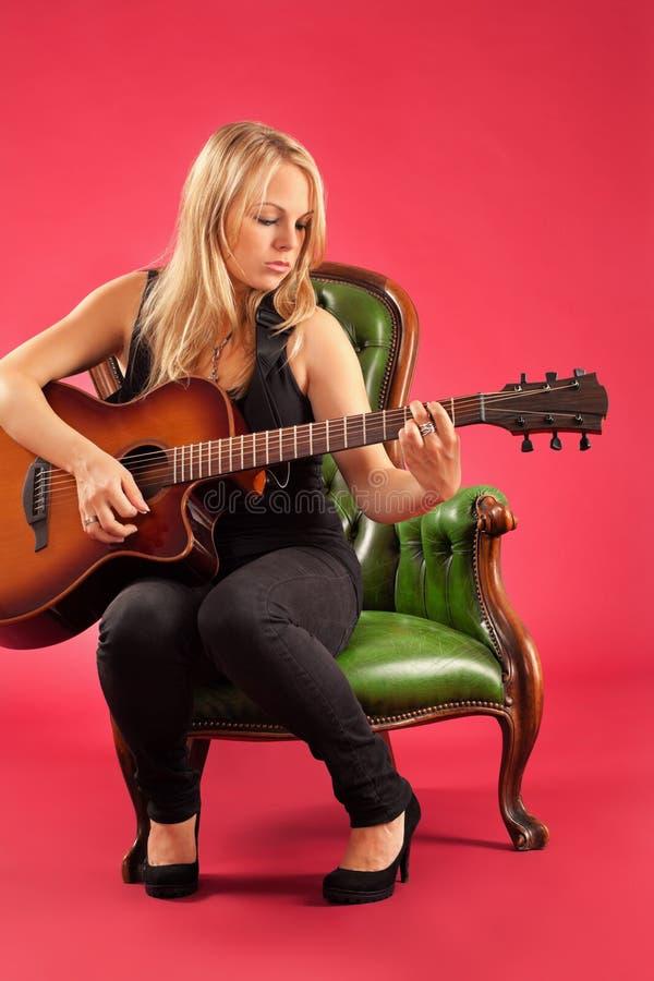 Aantrekkelijke vrouwelijke gitaarspeler stock foto