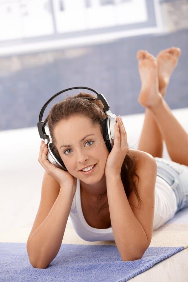 Aantrekkelijke vrouwelijke het luisteren muziek die op vloer leggen stock foto's