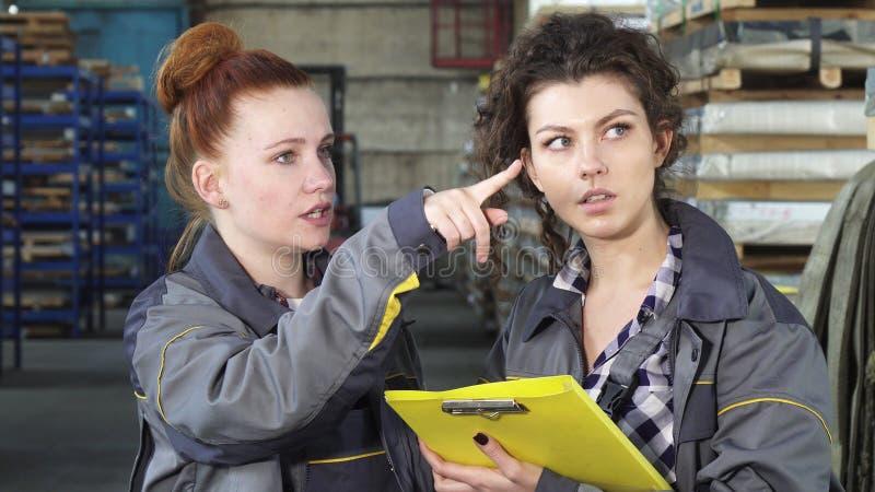 Aantrekkelijke vrouwelijke ingenieur die aan haar collega bij het fabriekspakhuis spreken royalty-vrije stock afbeelding