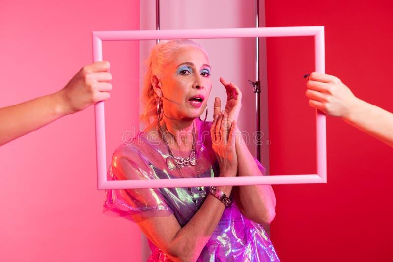 Aantrekkelijke vrouwelijke persoon die door wit kader kijken stock foto