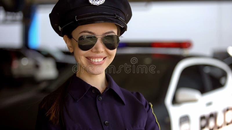 Aantrekkelijke vrouwelijke politieman die in eenvormig en zonnebril dichtbij auto glimlachen royalty-vrije stock foto