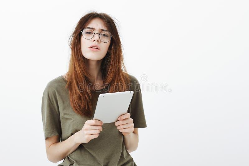 Aantrekkelijke vrouwelijke vrijwilligers het controleren gastlijst met gadget Studioportret van geconcentreerde slimme Kaukasisch stock fotografie