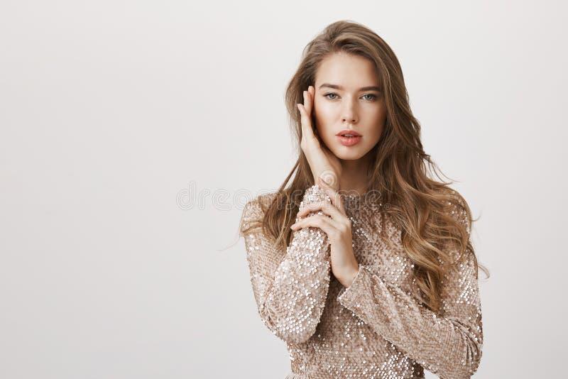 Aantrekkelijke vrouwelijke vrouw met mooi lang haar die zich in modieuze avondjurk, zacht wat betreft gezicht bevinden alsof  royalty-vrije stock afbeeldingen