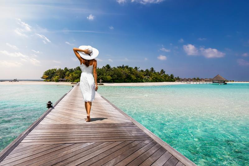 Aantrekkelijke vrouwengangen over een houten pier naar een tropisch eiland royalty-vrije stock afbeelding