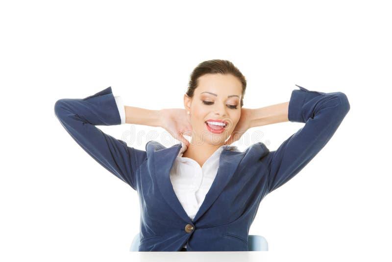 Aantrekkelijke vrouwenzitting met haar handen achter haar hals. stock foto's