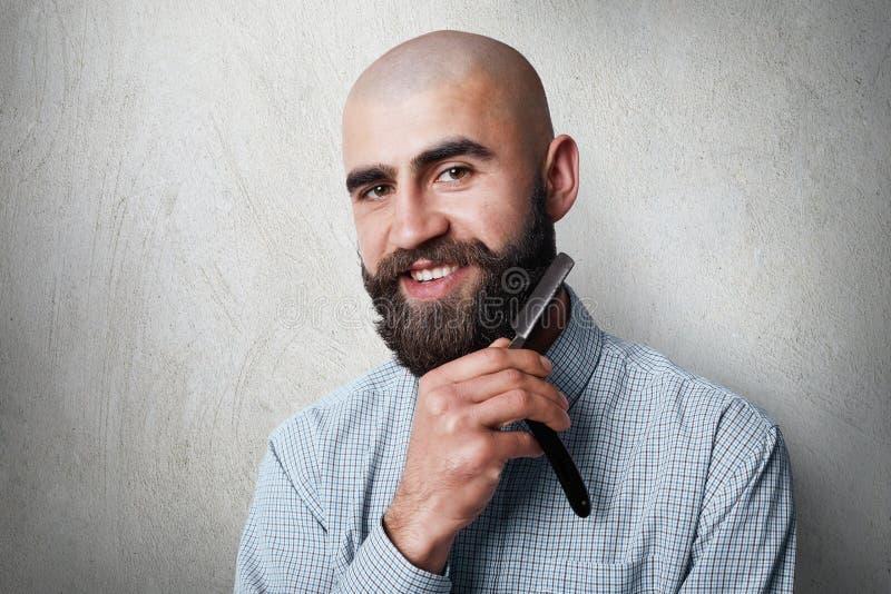 Aantrekkelijke yound balded kapper met dikke zwarte baard en snor glimlachend terwijl het houden van recht scheermes op zijn baar stock foto's
