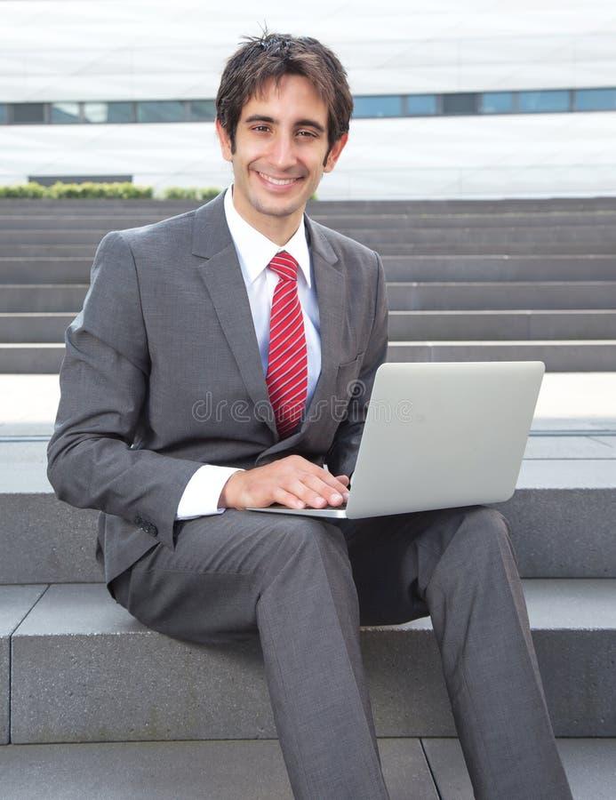 Aantrekkelijke zakenman met zwarte haar en computer stock foto's