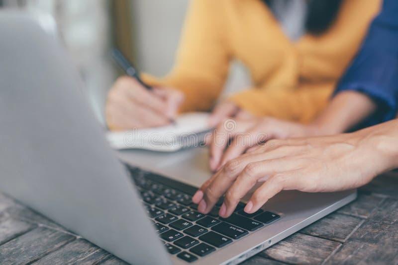 Aantrekkelijke zekere twee bedrijfsvrouwen in het slimme werken aan laptop creatief in haar werkplek en vrouwenhand die een pen h stock foto