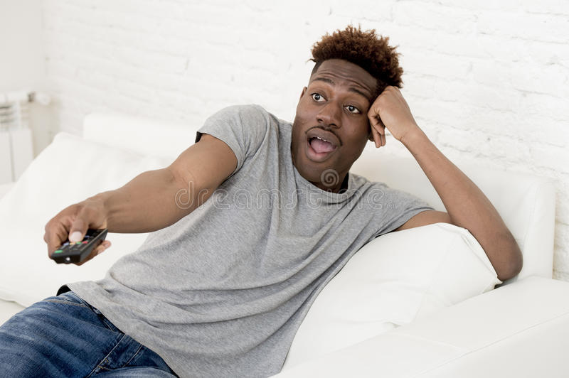 Aantrekkelijke zwarte Afrikaanse Amerikaanse de banklaag van de mensenzitting thuis het letten op televisie royalty-vrije stock fotografie
