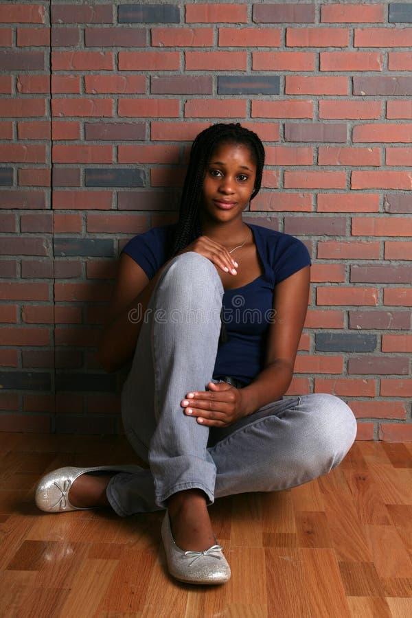 Aantrekkelijke zwarte tienerzitting op de vloer stock afbeeldingen