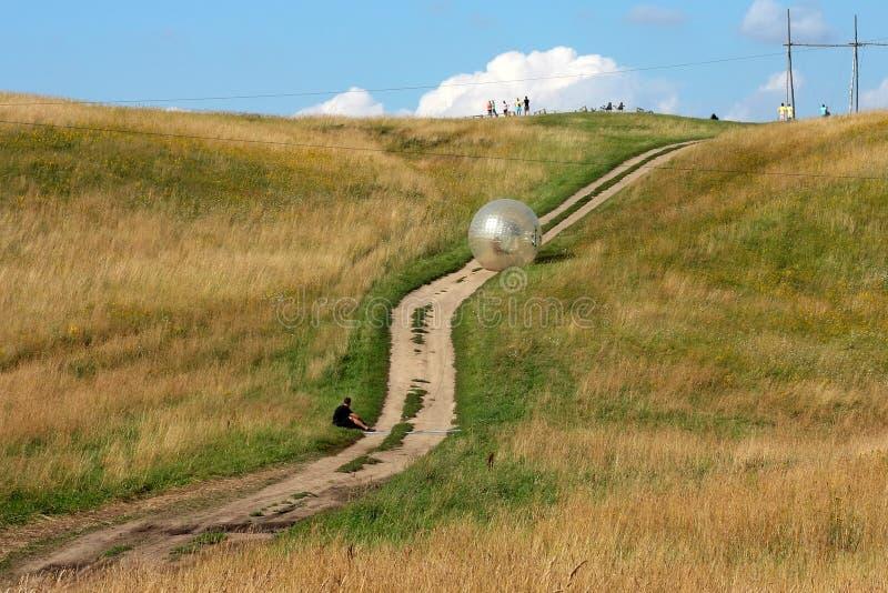 Aantrekkelijkheids zorbing bal die bergaf binnen orb rollen royalty-vrije stock foto's