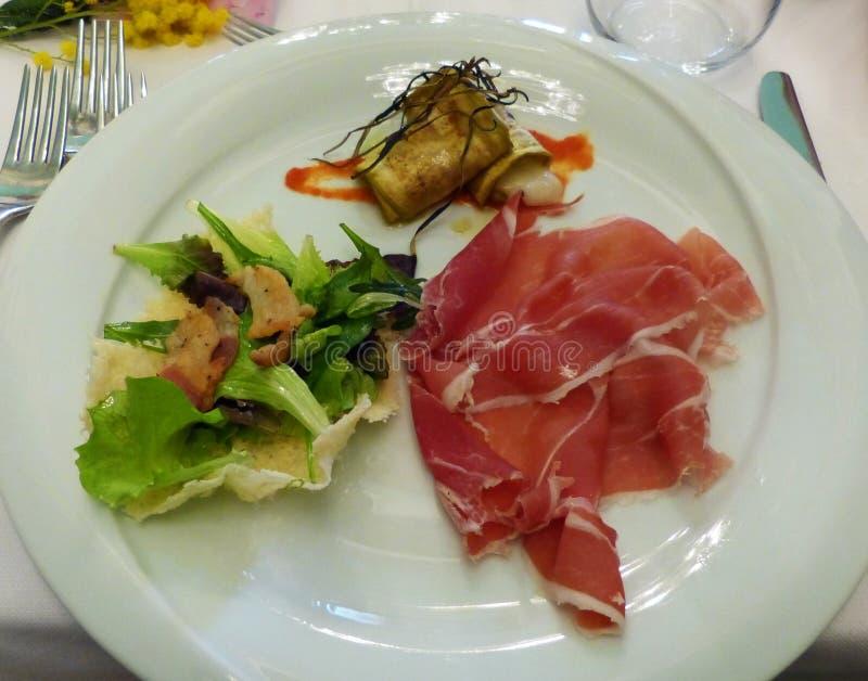 Aanzet met plakken van ham, auberginerollade met kaas, bacon en salade stock afbeelding