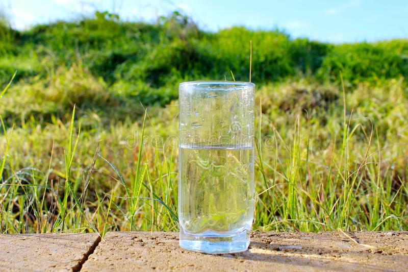 Aard in Israël Koud mineraalwater in een glas tegen de achtergrond van een mooi gebied en een blauwe hemel Regendruppels en Dauwd royalty-vrije stock foto