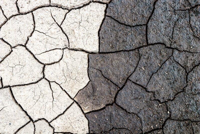 Aardachtergrond, grens van droge en natte gebarsten modder Concept tegengestelden, dark en licht royalty-vrije stock foto's