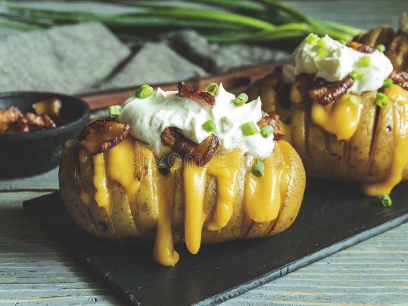 Aardappel in de schil met kaas, bacon en zure room wordt gevuld die geladen hasselback aardappels royalty-vrije stock fotografie