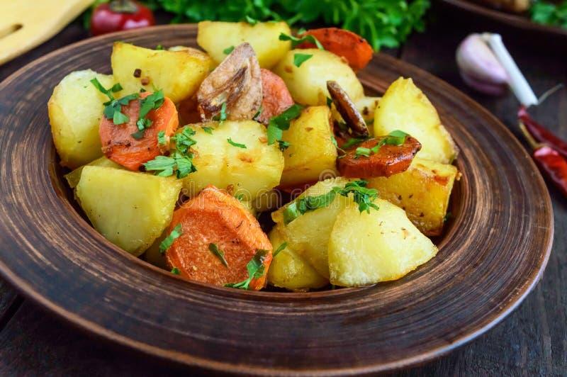 Aardappel in de schilstukken van, wortel ` op een plattelander, ` met kruiden in een kleikom op donkere houten achtergrond stock afbeeldingen