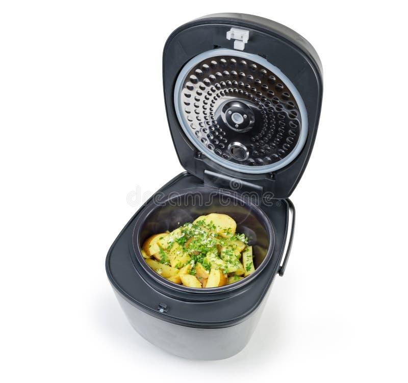 Aardappel in huishouden multi-kooktoestel wordt gebakken op witte achtergrond die royalty-vrije stock afbeeldingen
