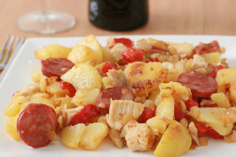 Aardappel met kip en worsten stock afbeelding