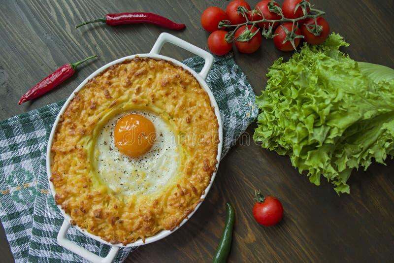 Aardappelbraadpan met bolognese Aardappel in de schilbraadpan met ei en geraspte kaas in een ceramisch ovaal bakselblad Houten da stock fotografie