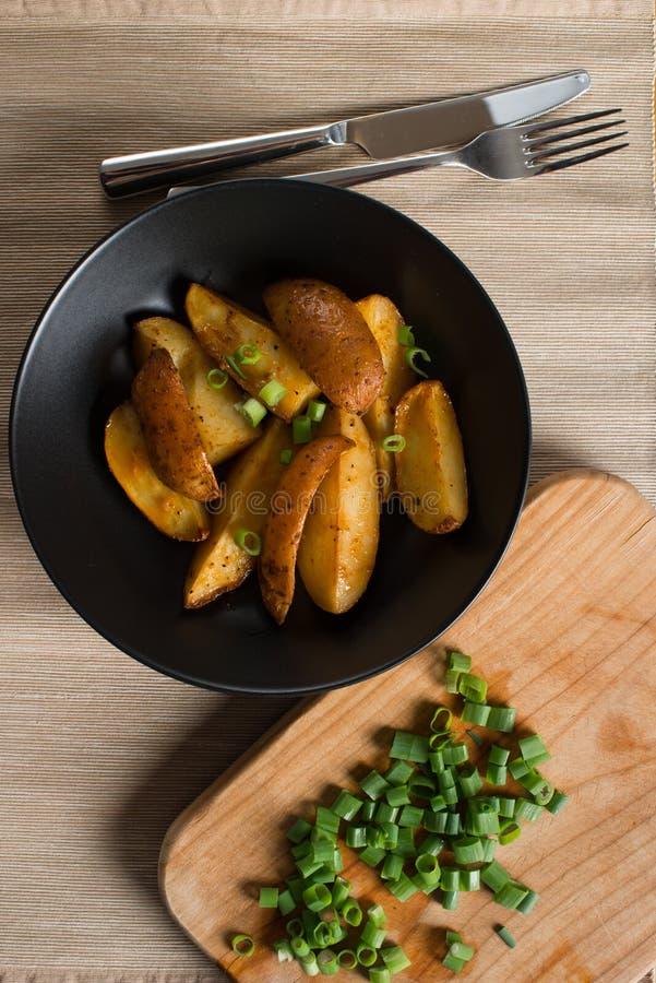 Aardappelen in de schil met groene uien royalty-vrije stock afbeeldingen