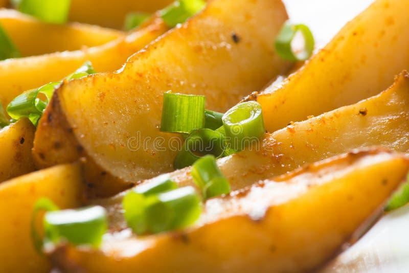 Aardappelen in de schil met groene uien stock afbeeldingen