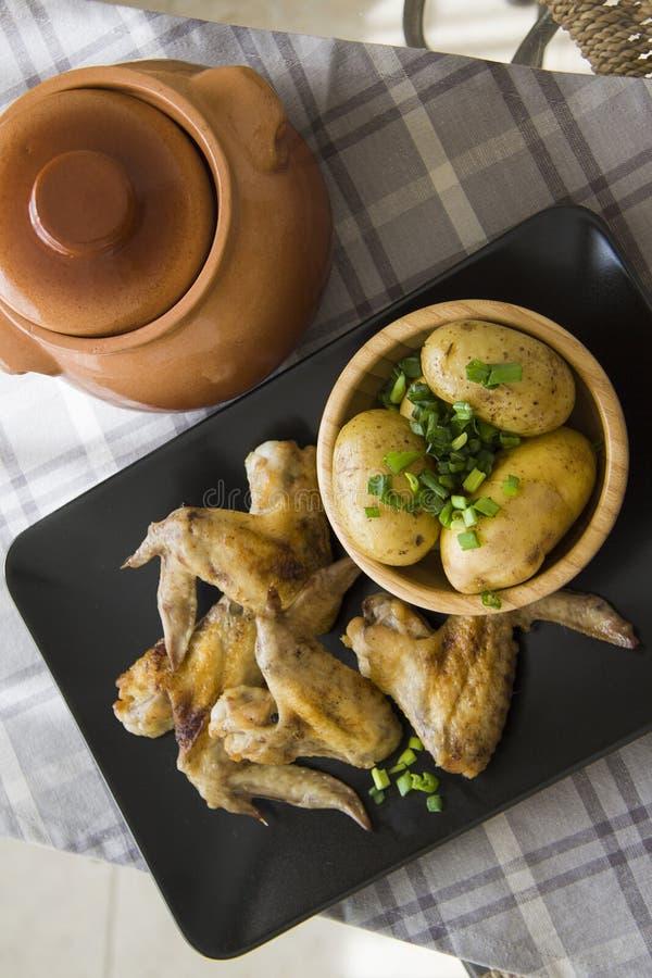 Aardappelgebraden gerechten en kippenvleugels stock fotografie