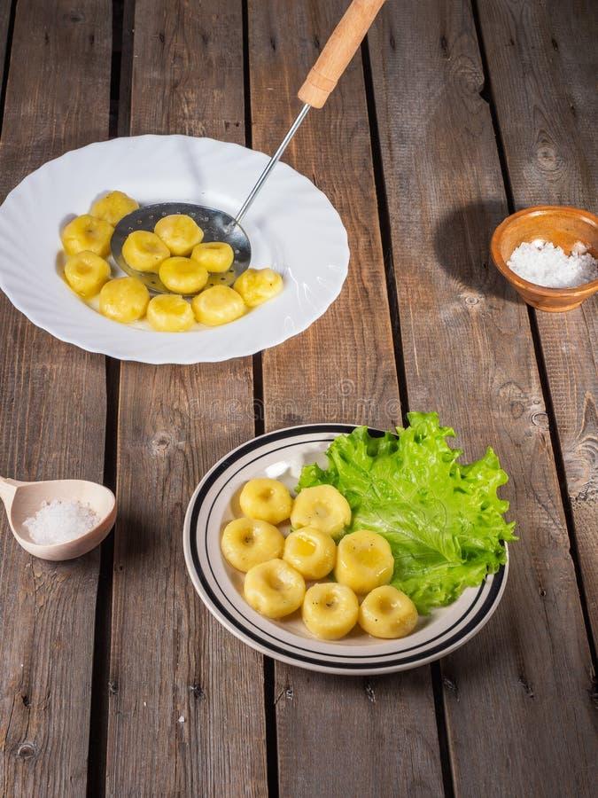 Aardappelgnocchi op twee platen, bladeren van verse bladsla op lichte platen op een oude planklijst Dichtbij een houten lepel met royalty-vrije stock fotografie