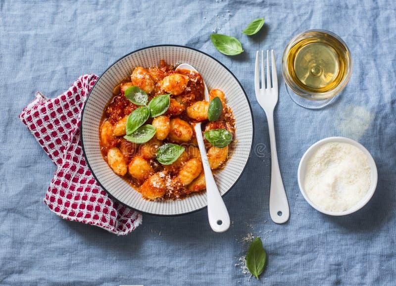 Aardappelgnocchi in tomatensaus met basilicum en parmezaanse kaas en een glas witte wijn op blauwe achtergrond, hoogste mening It royalty-vrije stock foto's