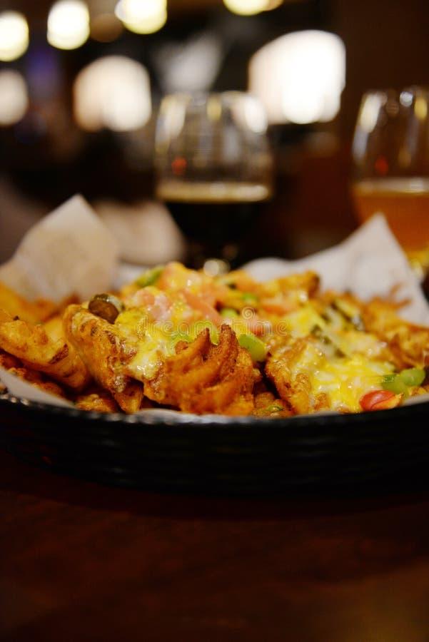 Aardappelnachos in bar stock afbeelding