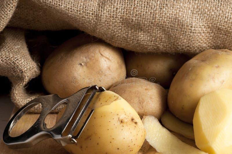 Aardappels die uit de jute zijn stock afbeeldingen