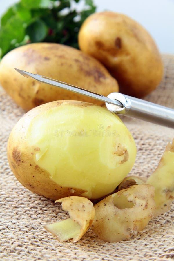 Aardappels met een mes om de groenten schoon te maken royalty-vrije stock foto's