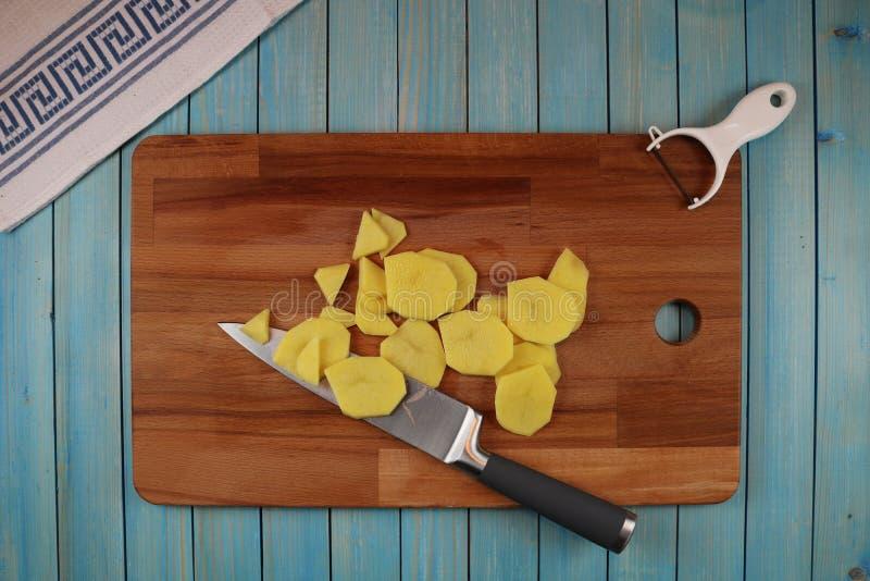 Aardappels op een houten raad voor scherpe groenten stock afbeeldingen