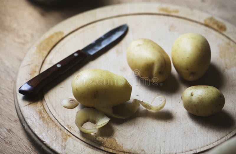 Aardappels op een scherpe raad worden gepeld die stock afbeelding