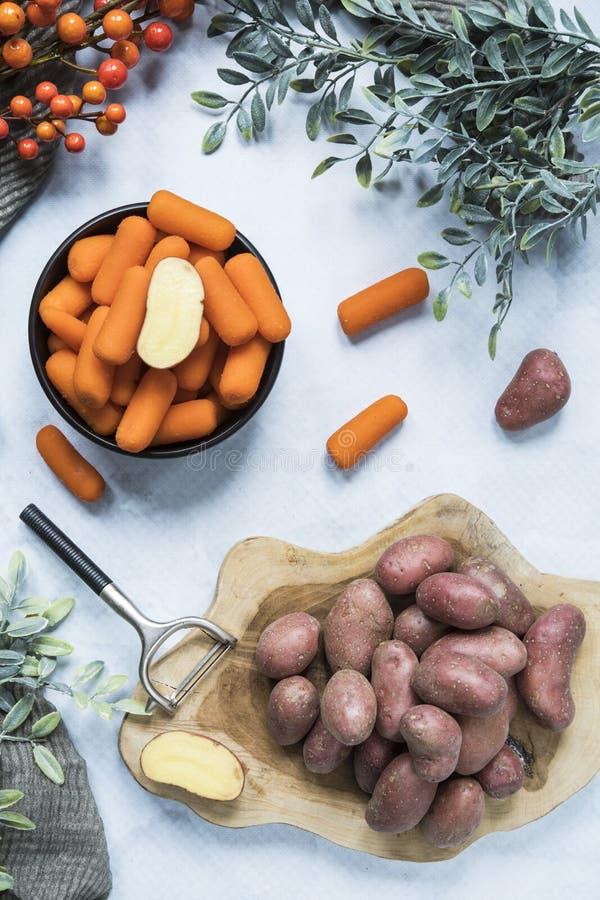 Aardappels op scherpe raad en wortelen in kom royalty-vrije stock fotografie