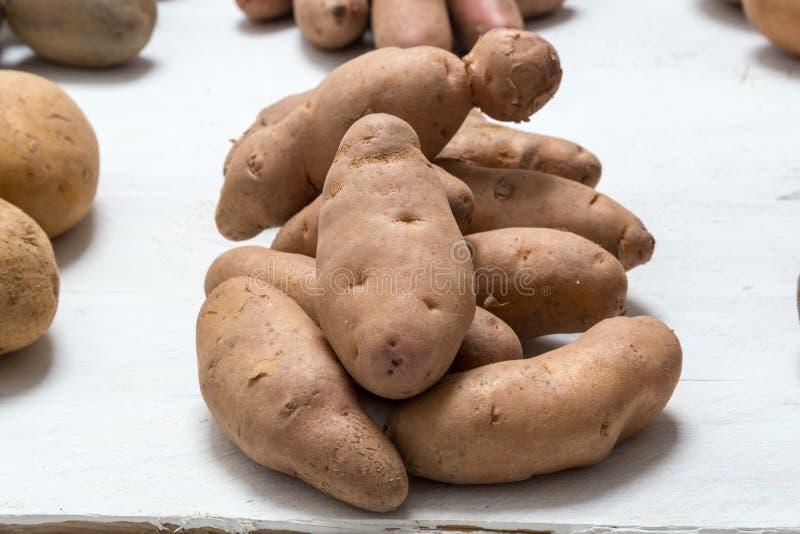 Aardappels op wit houten raadsconcept stock foto